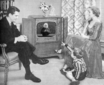 Bourgeois 50s living room with Mummy & Daddy; boy pointing at Einstein on the television